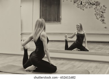 young sporty girl sitting in One Legged King Pigeon exercise, working out, wearing sportswear, doing stretching exercises during the training in fitness club. Sepia