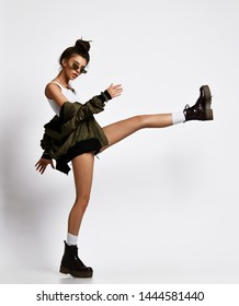 Young sporty girl in sportwear fighter kicking with the leg hit in black boots and green jacket on gray background