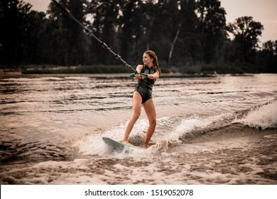 Young sporty girl in swimsuit wakesurifing with rope in the river near forest