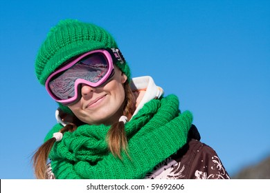 Young sporty girl wearing ski mask and hat. Winter vacation in Alps