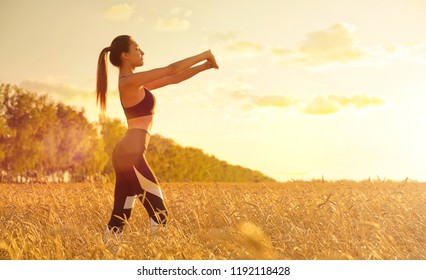 Young sporty girl in wheat field