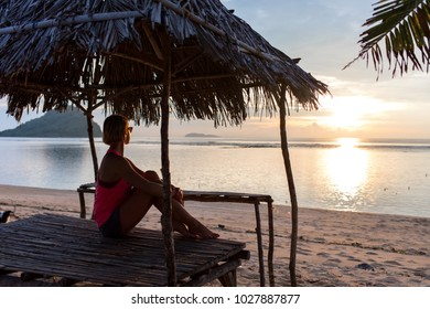 young sporty girl or woman sitting on the beach and watching sunset, thinking or relaxing. romantic evening vacation mood