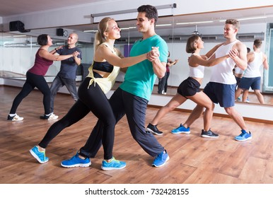 Young sporty girls and men dancing salsa steps