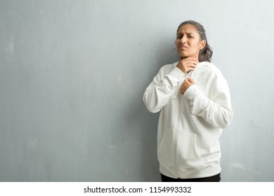 Young sporty indian woman against a gym wall with a sore throat, sick due to a virus, tired and overwhelmed
