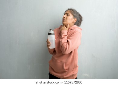 Young sporty indian woman against a wall with a sore throat, sick due to a virus, tired and overwhelmed. Drinking cold and refreshing water.