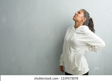 Young sporty indian woman against a gym wall with back pain due to work stress, tired and astute