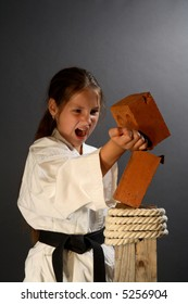Young sporty karate girl breaking a brick on gray background