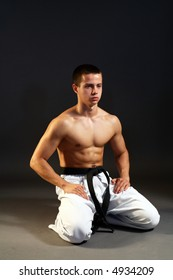 Young sporty karate man doing special exercise on gray background