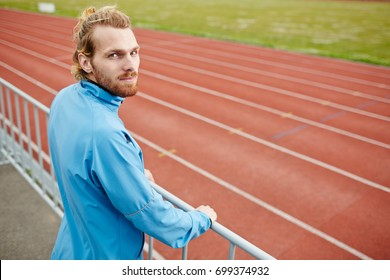 Young sporty man in activewear spending leisure by training on stadium