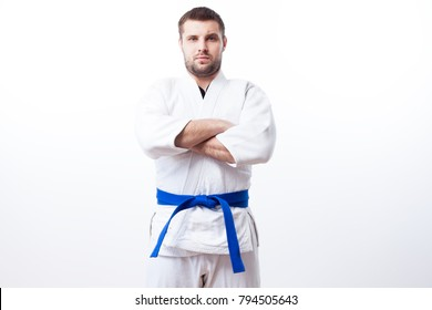 Young sporty man with dark hair in a white kimono with blue belt for sambo, jiu jitsu, judo stands with his arms crossed on a white isolated background, front view