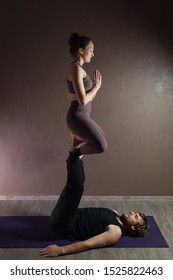 Young sporty man and girl practicing yoga, meditating in yoga pose, working out, wearing sportswear, indoor full length, brown yoga studio