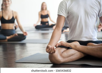 Young sporty man and a group of sporty people practicing yoga lesson, doing Padmasana exercise, Lotus pose, working out, indoor close up photo, studio. Healthy, mindful lifestyle concepts