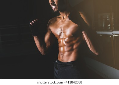 Young sporty man in the gym. Male boxer. Training. Close up man body