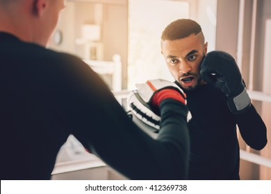 Young sporty man in the gym. Male boxer. Training. Mood, motivation, coach,sparring, competition - sport concept.