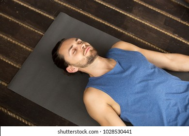 Young sporty man lying in Dead Body exercise or Corpse pose with his eyes closed, Savasana pose, working out, resting after practice, indoor close up, studio, top view