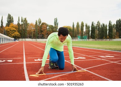 Young sporty man are ready to run on racetrack. Fit well formed people  at large nice modern stadium