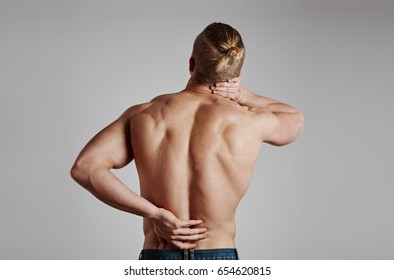Young sporty man touching his painful back over grey background.