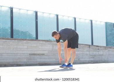 Young and sporty man training outdoor in sportswear. Sport, health, athletics.