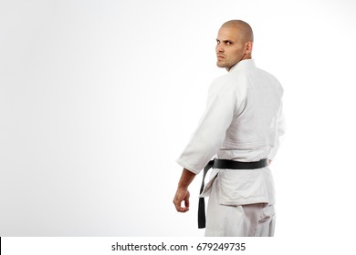 Young sporty man in white kimono for sambo, judo, jujitsu posing on white background, stands with back