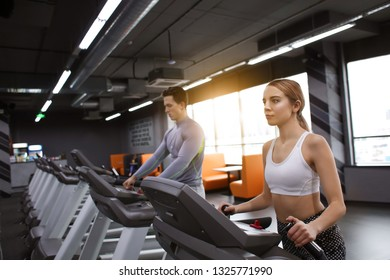 Young sporty man and woman training in modern gym