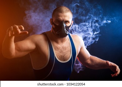 A young sporty man wrestler in a green sports shirt and trainig mask wrestling against a blue vape smoke background on a black isolated