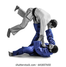 Young sporty men practicing martial arts on white background