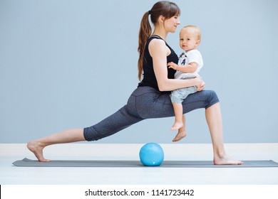 young sporty mother does physical yoga or pilates exercises together with her toddler baby son over gray background. Fitness, happy maternity and healthy lifestyle concept.