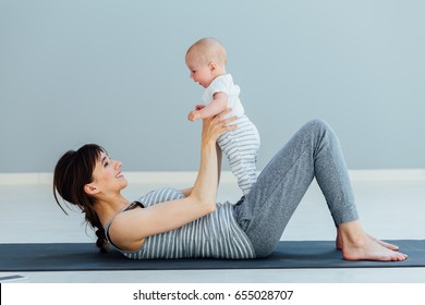young sporty mother does physical yoga or pilates exercises together with her baby son over gray background. Fitness, happy maternity and healthy lifestyle concept.