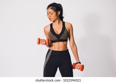 Young sporty muscular woman holding dumbbells isolated over white background. Woman in sport clothing exercising