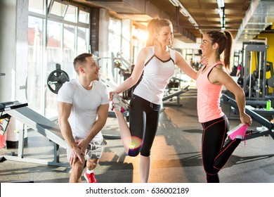 Young sporty people doing stretching exercises at gym.
