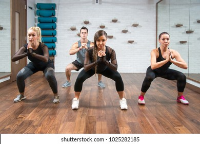 Young sporty people exercising together in sumo squat pose at gym.