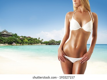 Young, sporty, sexy and beautiful girl in swimsuit resting on exotic beach in summer