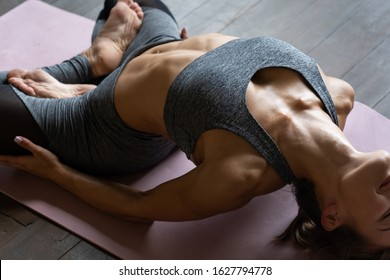 Young sporty slim fit woman trainer doing exercise practice hatha yoga instructor training matsyasana pose backbend fish position lotus legs on mat wooden floor in yoga studio, close up view