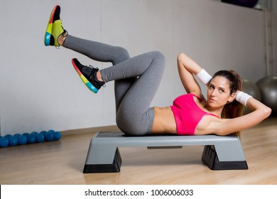 Young sporty woman in activewear making crunches in gym during training
