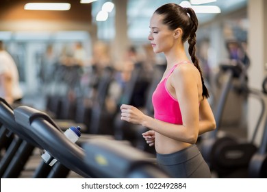 Young sporty woman in activewear running on treadmill in gym