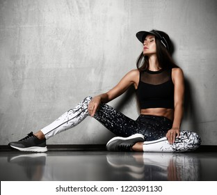 Young sporty woman after gymnastics stretching fitness exercises workout sitting on floor on dark wall background