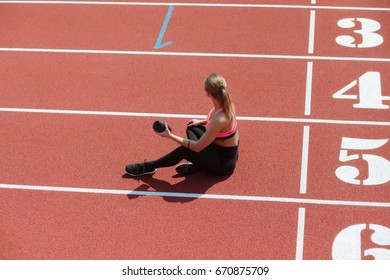 Young sporty woman athlete in sportswear sitting and keep shake with water on stadium track