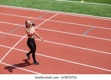 Young sporty woman athlete in sportswear drinking water or protein cocktail from shake on stadium track, workout concept