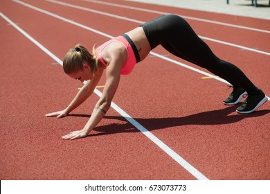 Young sporty woman athlete in sportswear stretches on stadium track, outdoor workout