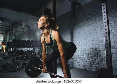 young sporty woman doing deadlift indoors in a gym with the barbell