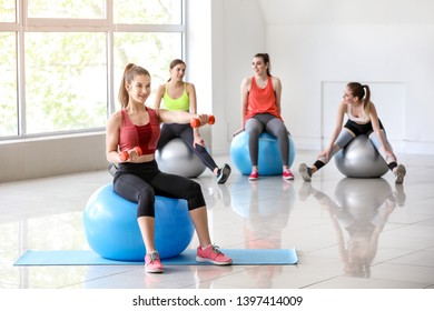 Young sporty woman doing exercises with fitball in gym