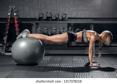 young sporty woman doing fitness exercise plank in gym interior with fit ball