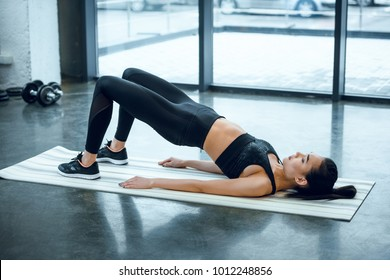 young sporty woman doing hip raise at gym