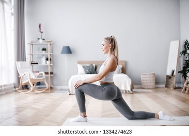 Young sporty woman doing morning exercise in living room. Fit girl.