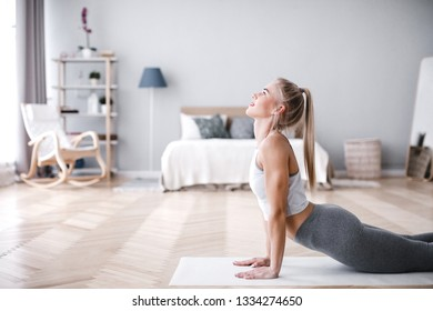 Young sporty woman doing morning exercise in living room on mat. Fit girl.