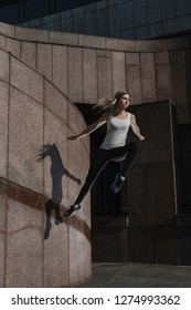 Young sporty woman doing parkour in city. The girl is engaged in freerunning.