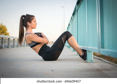 Young sporty woman doing sit ups on a sidewalk.