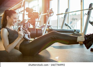 Young sporty woman doing situps with weights in gym