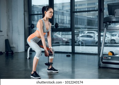 young sporty woman doing squats with weight plates at gym