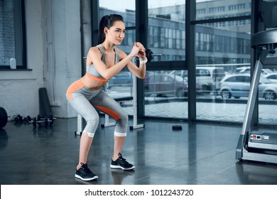 young sporty woman doing squats at gym
